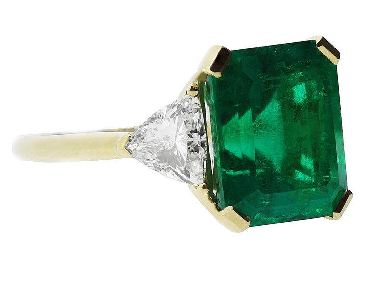 This impressive vintage emerald with the most beautiful emerald green colour and diamond three stone ring is crafted in solid 18 K yellow gold.  A magnificent 7.75 ct certified Colombian emerald and it is flanked by 2 sparkling triangle bulged side