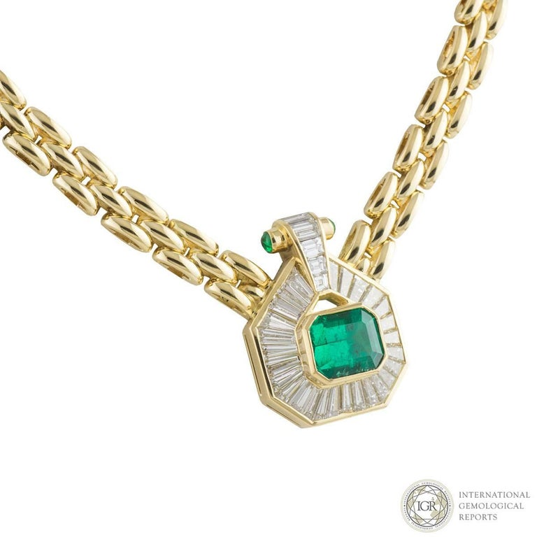 A beautiful 18k yellow gold emerald and diamond necklace. The necklace comprises of an octagonal emerald cut emerald with a weight of 2.84ct, with a strong bright green hue throughout, Type III and VS clarity. Surrounding this emerald are round