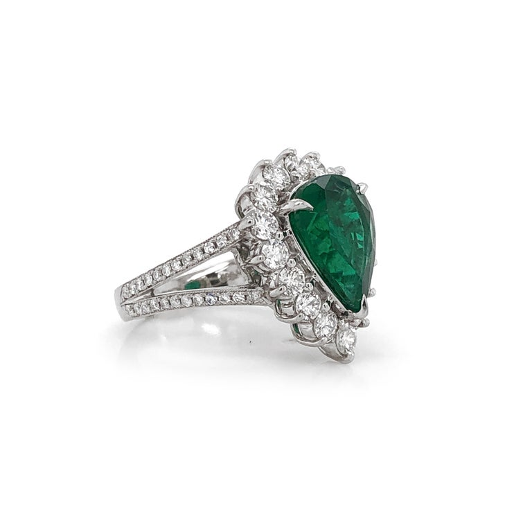 Elegantly styled pear cut green Zambian emerald 3.66 carat center stone.  Accented by round diamonds 1.36 in total.  Diamonds are white and natural and in G-H Color Clarity VS. Platinum 950 metal.  Beautiful cocktail and engagement ring hybrid.