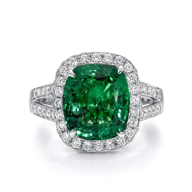 Emerald engagement ring featuring a 4.66 carat vibrant Emerald cushion cut, accented by a total of 1.06 carats of round brilliant diamonds, in 18K white gold. Emerald ring size 6.5. Resizing is complimentary upon request.  The C. Dunaigre gem