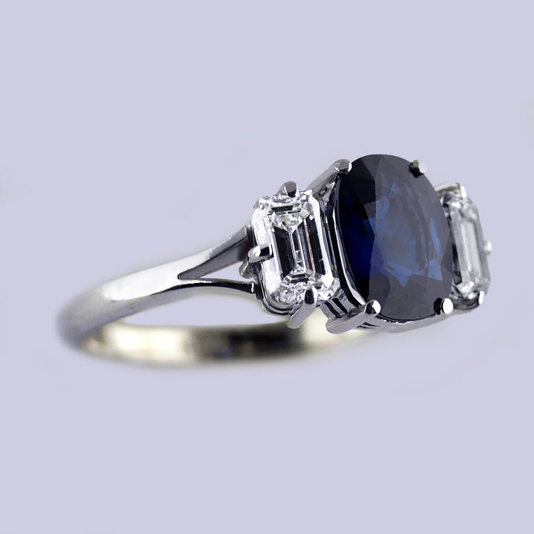 Vintage ring with a natural, untreated, blue sapphire, handmade in England, circa 1960.  Central Blue sapphire, cushion cut, weighing 1.51ct, certified, natural untreated colour.   The sapphire set with a baguette cut diamond on each side, with a