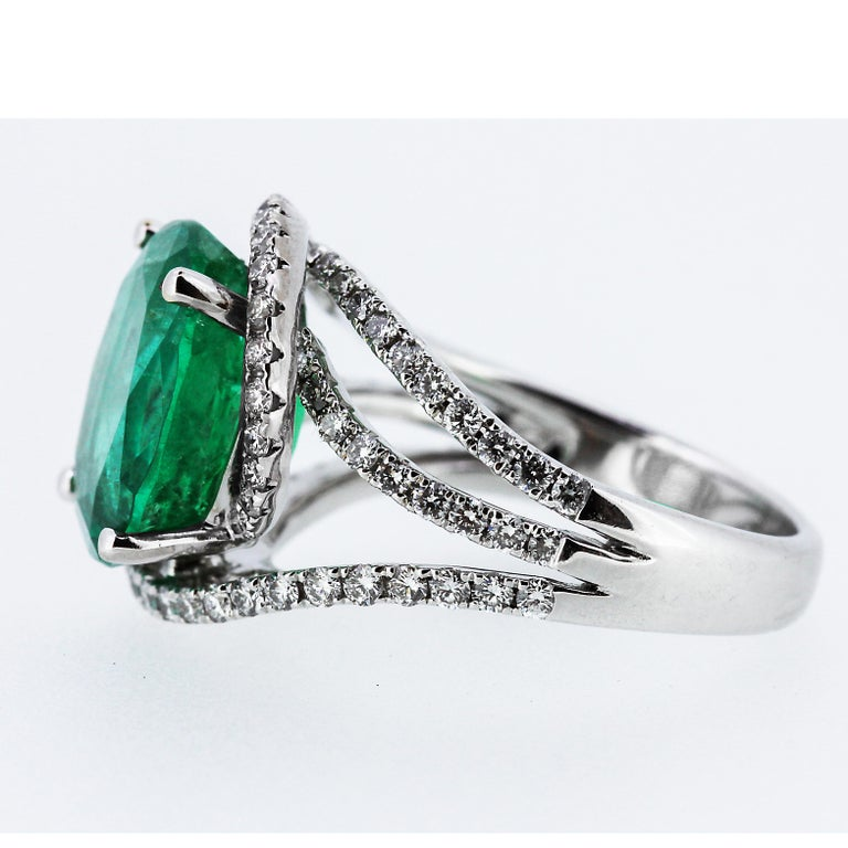 A remarkable fine Colombian emerald set in 18 carat white gold and surrounded by beautifully design round brilliant cut diamonds. The 5.3 carat emerald shows very good colour vivid green and highly transparent.  1 x Oval shape faceted emerald,