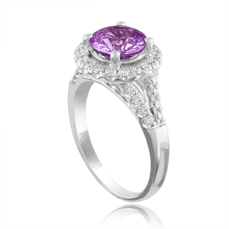 Exquisite Pink Sapphire Halo Ring The ring is 18K White Gold Ring The sapphire is a round 2.18 Carats The sapphire is Pink in color No HEAT The stone is certified by LAPIS. The Sapphire changes color depending on light. There are 0.60 Carats in