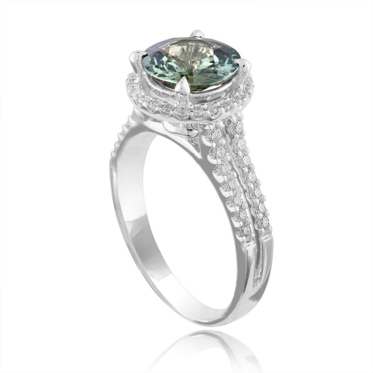 Exquisite Bluish Green Sapphire Halo Ring The ring is 18K White Gold Ring The sapphire is a round 2.56 Carats The sapphire is Bluish Green in color No HEAT The stone is certified by LAPIS. The Sapphire changes color depending on light. There are