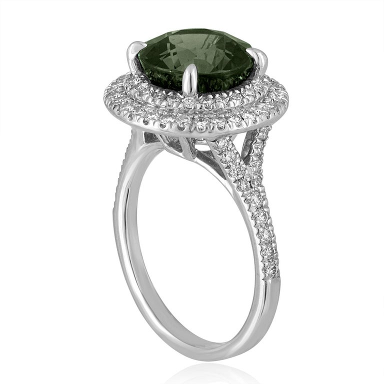 Exquisite Sapphire Surrounded by Double Diamond Halo The ring is 14K White Gold There are 0.80 Carats in Diamonds F VS The Round Sapphire is Bluish Green 5.27 Carats No Heat The Sapphire is Certified By LAPIS The ring is a size 6.75, sizable. The