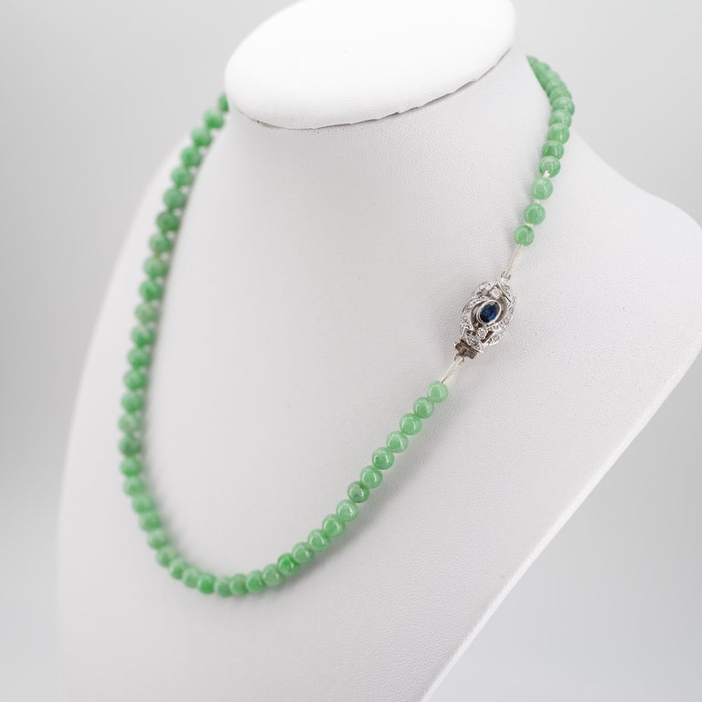 This refreshing, bright minty green jadeite jade necklace from the Art Deco era is just sixteen inches in length and features an elegant clasp of 18K white gold centered with a gemmy little natural oval cut sapphire of about one-quarter carat. Small