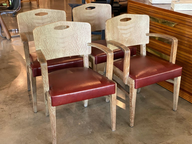 Set of four Art Deco oak chairs with cerused finish designed by famed Swiss architect Michel Polak. Newly upholstered seats in oxblood red/maroon leather. Likely an early fabrication by Joseph de Coene. Brussels, 1930-1935 Also sold as a pair see