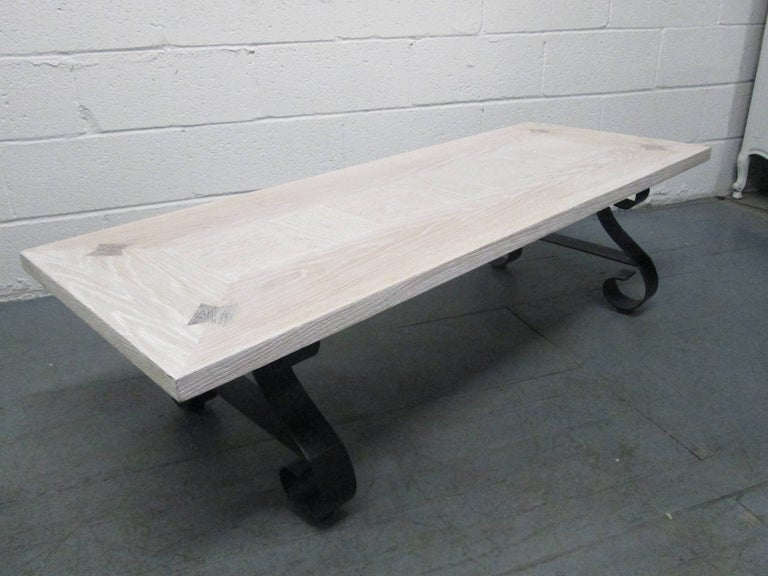 Cerused oak coffee table. The table has rosewood dials to the top and a sculpted wrought iron base.
