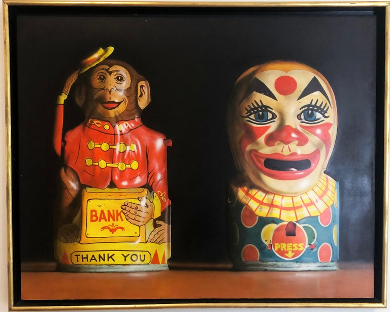 'Two Toy Banks' 1982 by American artist Cesar J. Santander. Oil on panel, 27.75 x 34.5 in. This painting features a finely detailed monkey and clown piggy banks rendered in rich colors of red, yellow, blue, brown and black. Framed in a gold