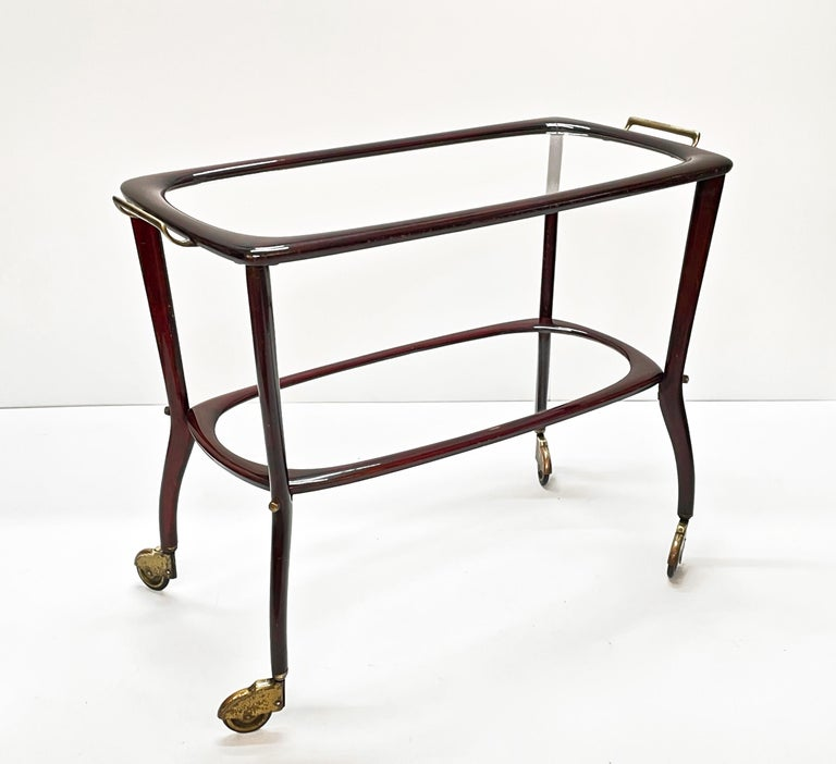 Amazing midcentury wood and glass trolley bar cart. This fantastic item was produced in Italy during the 1950s by Cesare Lacca.  The smooth lines are just fantastic and the mix with the crystal glass shelves make this item light and delicate. The