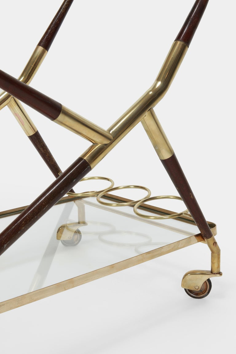 Beautiful Cesare Lacca serving trolley, made in Italy in the 1950s. Very elegant and simple shape with a solid brass frame and dark brown mahogany lacquered on high gloss with slight signs of wear, original glass shelves, one of which can be used as