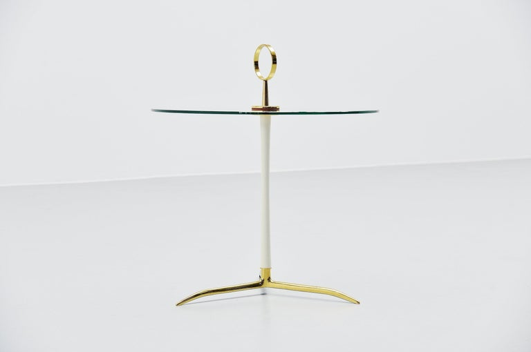 Sophisticated side table designed and manufactured by Cesare Lacca, Italy 1950. This table has a solid brass tripod base and white bar. It has a round brass handle to easily grab it and move it while vacuum cleaning for example, or use it elsewhere.