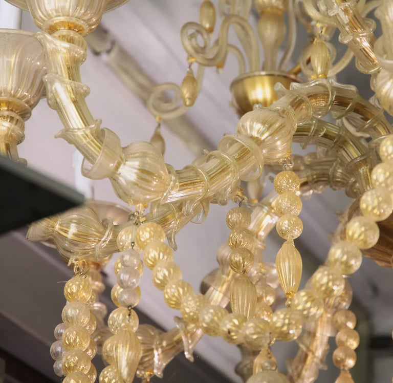 Grand Ca Rezzonico chandelier. All made in clear glass with 24-karat gold leaf embedded into glass. The use of gold leaf highlights and bring preciousness to the chandelier. There are two highlights on this chandelier, the first is a row of glass