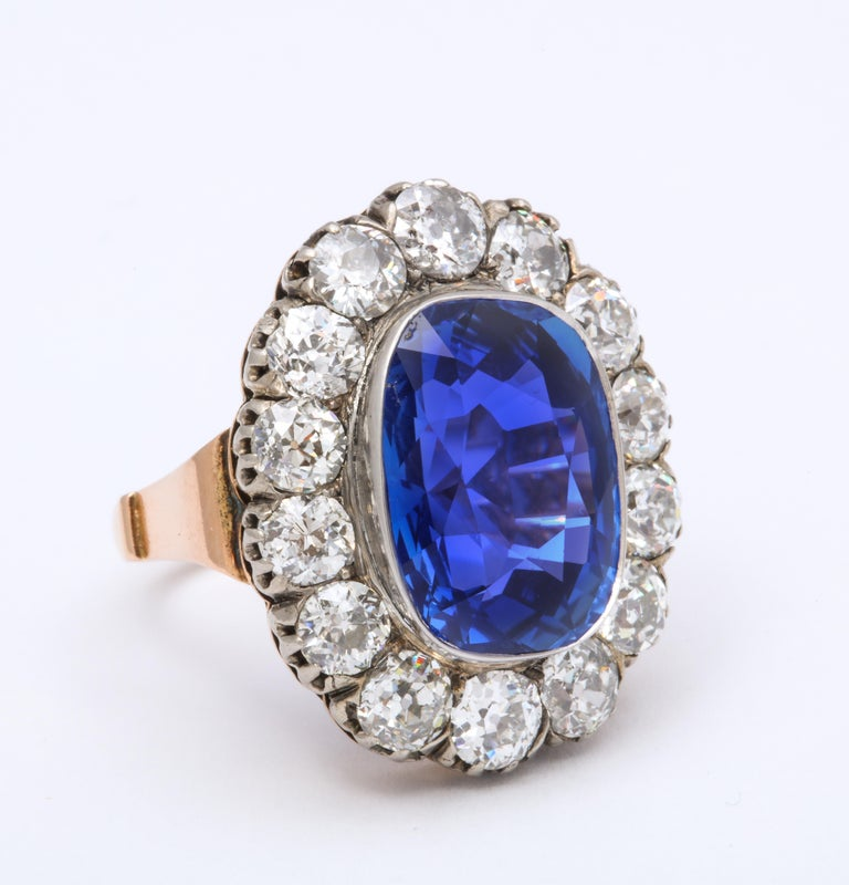 Circa 1880's Ceylon Sapphire and Diamond ring in 15k Yellow Gold, stamped KS. There are 14 old mine cut diamonds totaling 4.50 carats. The center showcases an 11.70 carat cushion cut natural Ceylon Sapphire.  Circa 1850. Size 6.  AGL report