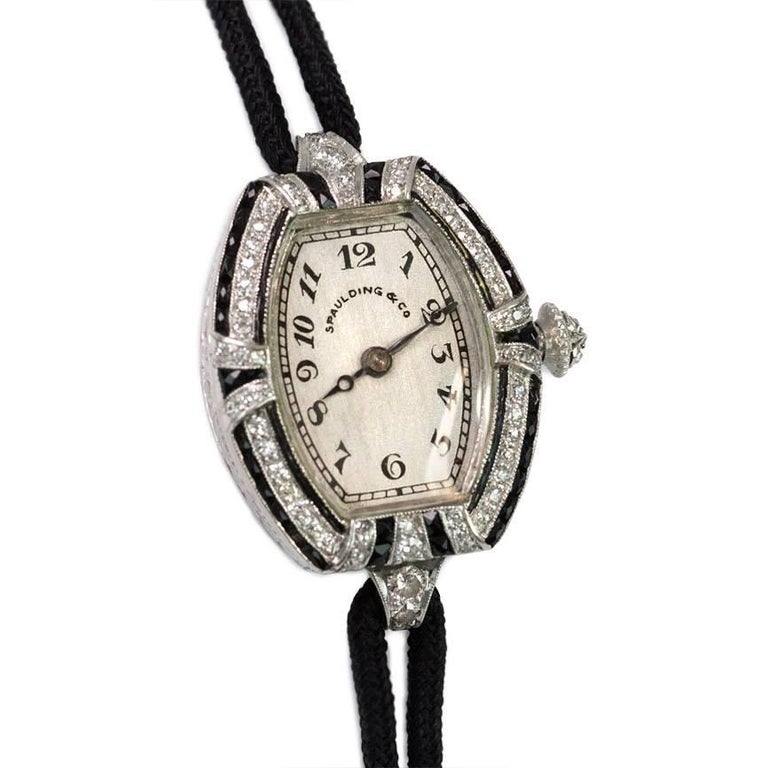 Art Deco diamond and onyx lady's watch with tonneau-shaped face, in platinum.  Retailed by Spaulding & Co.  Movement signed C.H. Meylan, Brassus, Swiss, 18 jewels, 31888.