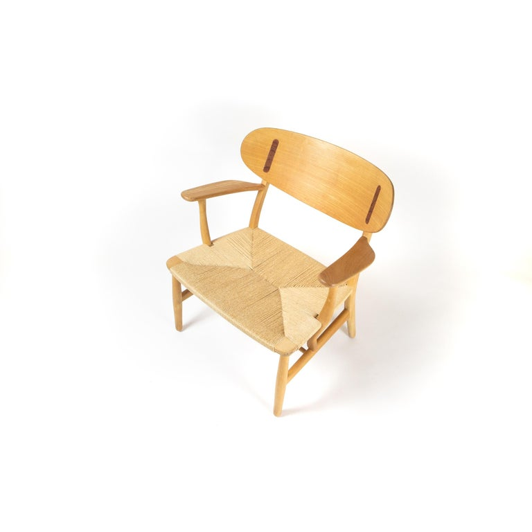 CH22 lounge chair by Hans J Wegner for Carl Hansen & Søn, Denmark. In excellent condition the chair is in beech with teak inserts and has been recently cleaned and treated with a soap finish. The paper cord seat is in excellent condition. This