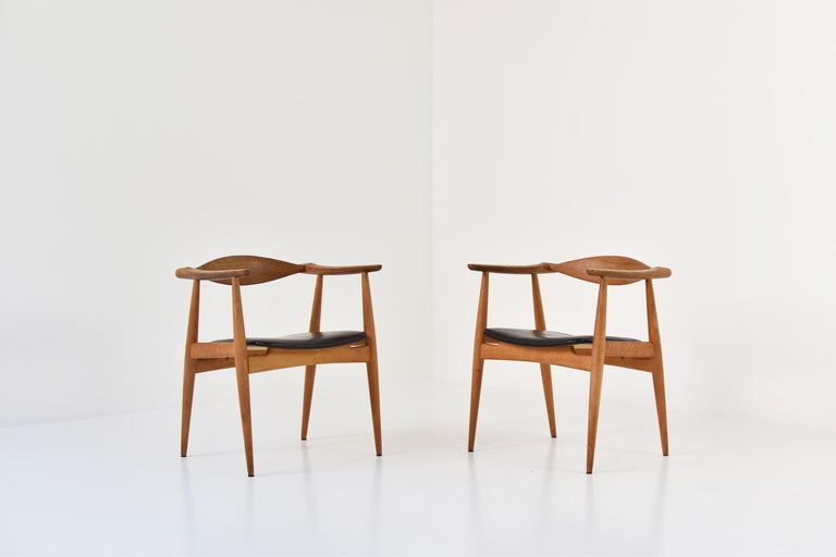 An amazing pair of CH35 chairs designed by Hans Wegner for Carl Hansen and Son, Denmark, 1950s. These sculptural armchairs features oak frames with the original (lovely) patinated black leather seats. Labeled underneath. Masterpiece!