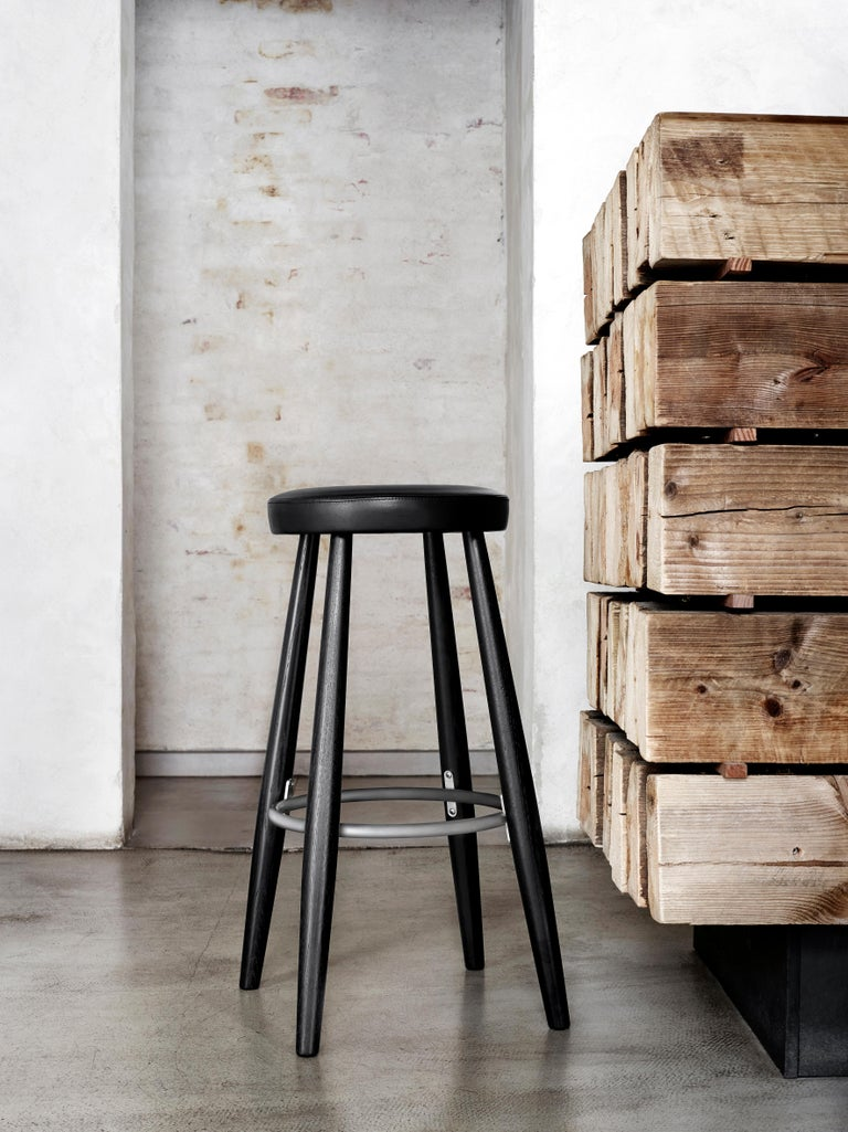 The CH56 barstool in solid wood, leather and stainless steel designed by Hans J. Wegner in 1985 is simple, practical and superbly-crafted for great comfort and an appealing atmosphere in any space.  Dimensions: 15.4in D x 15.4in W x 29.9in H The