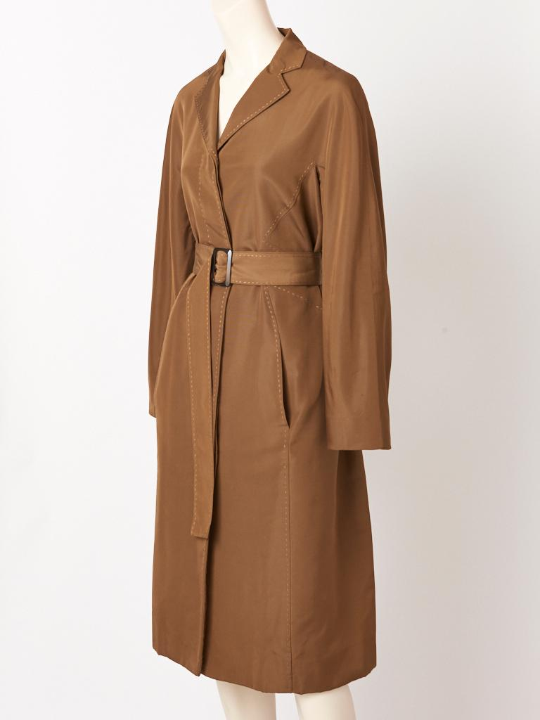 Chado Ralph Rucci, taffeta faille, bronze tone, belted coat, having a small lapel collar, hidden button closures, (buttons are tortoise) a double vent at the back, slash pockets, and contrasting, signature, top stitching detail throughout. Coat is