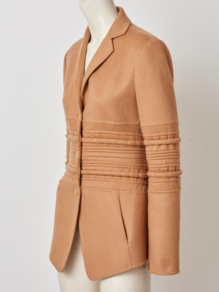 Chado Ralph Rucci, camel tone, fitted cashmere jacket/blazer having a 3 button closure, narrow notched lapel collar and horizontal, Tapunto and top stitching detail at the torso and middle sleeves. Slanted slash pockets at the hips.
