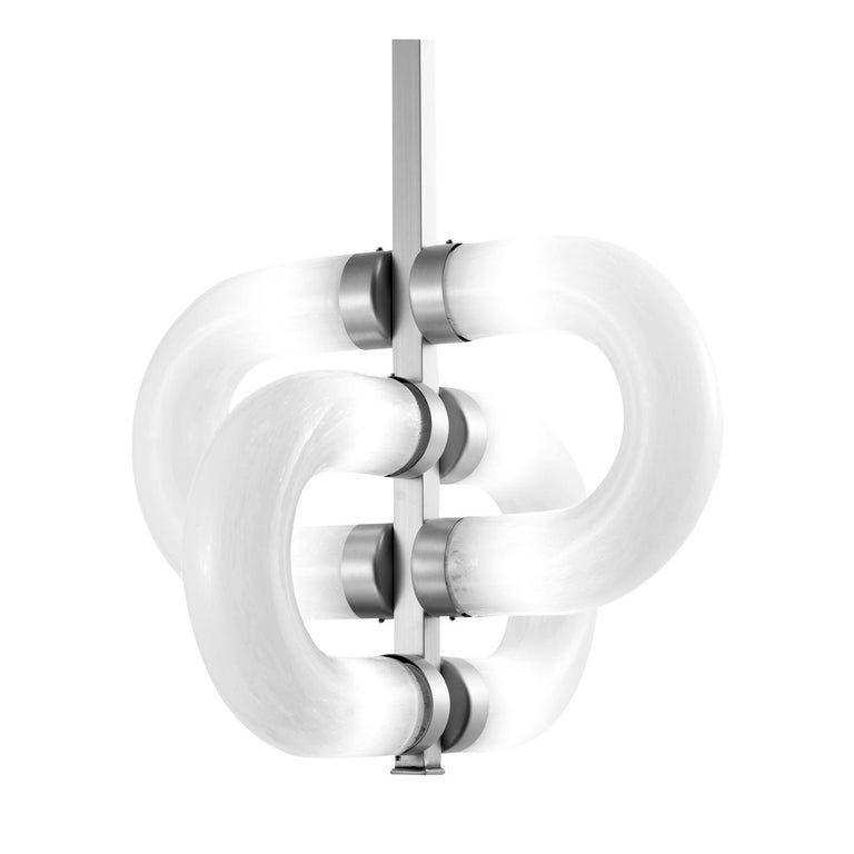 The elementary shape of a chain inspired this mesmerizing glass pendant lamp. A central metal frame with a satin brass finish supports the curved, cylindrical diffusers in white glass, each hosting two tubular LED bulbs (E14 and 4W) and seemingly