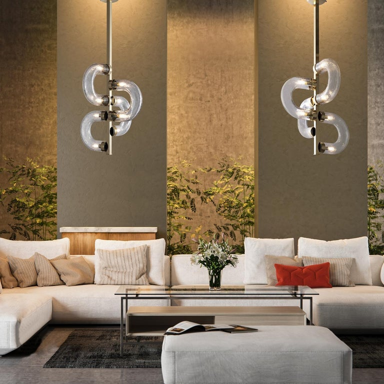 A superb contemporary view of lighting design inspired this charming pendant lamp whose crafting is carried out by master glassmakers. The motif of chains characterizes the Silhouette of this piece. The vertical, gold-plated metal frame is a support