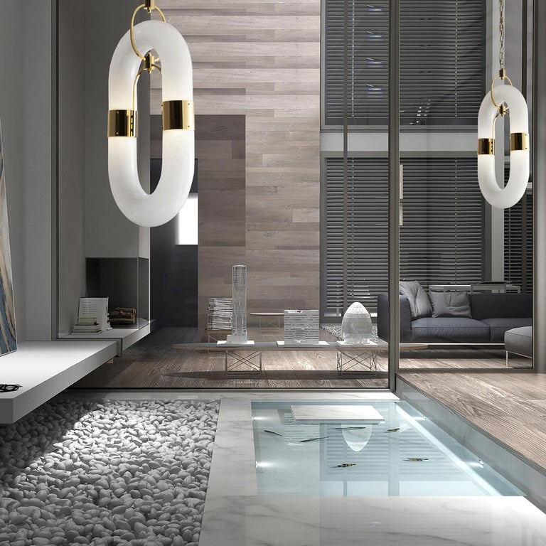 A striking piece exuding its deeply contemporary soul, this exquisite pendant lamp showcases a continuous elliptical silhouette composed of a cylindrical shade in white glass hosting the four chip LED sources (15W 230V) with gold-plated metal