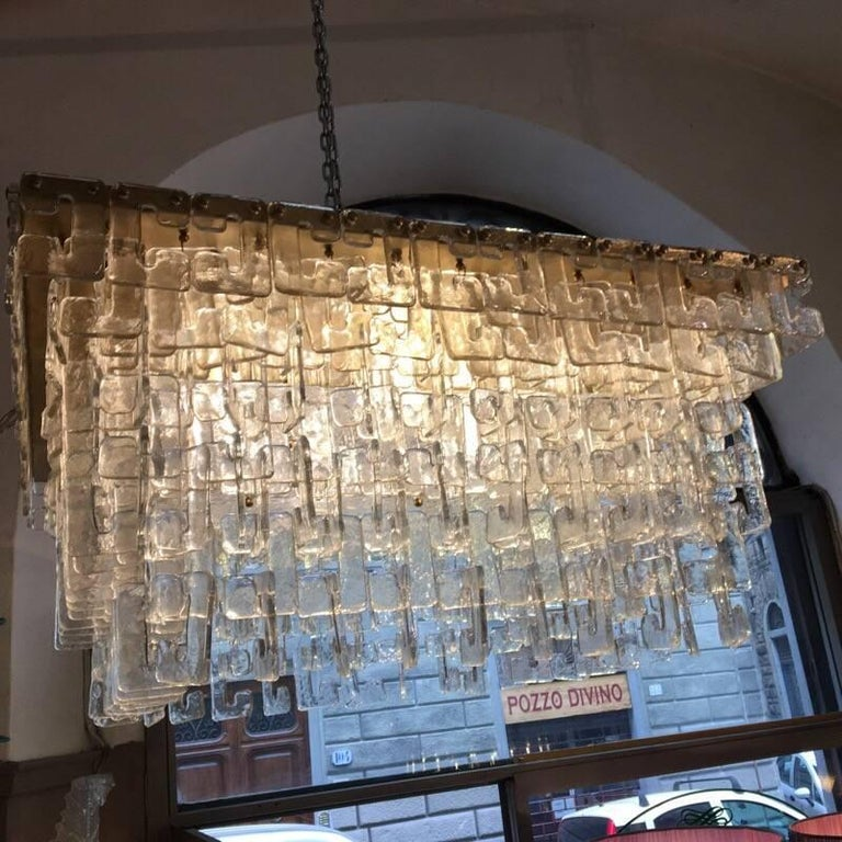 Chain link Murano C-shaped clear glass chandelier and brass structure. The hand blown clear glasses hook on each other with waterfall effect. The chandelier weighs about kg 100 and it has four light bulbs.