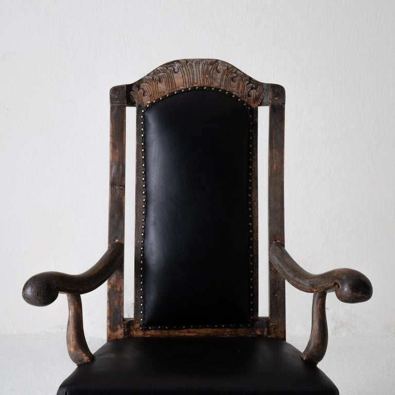 Chair armchair Swedish baroque black original paint, Sweden. An armchair during the baroque period in Sweden in a generous size. Stripped to its original finish with a beautiful leather as upholstery.