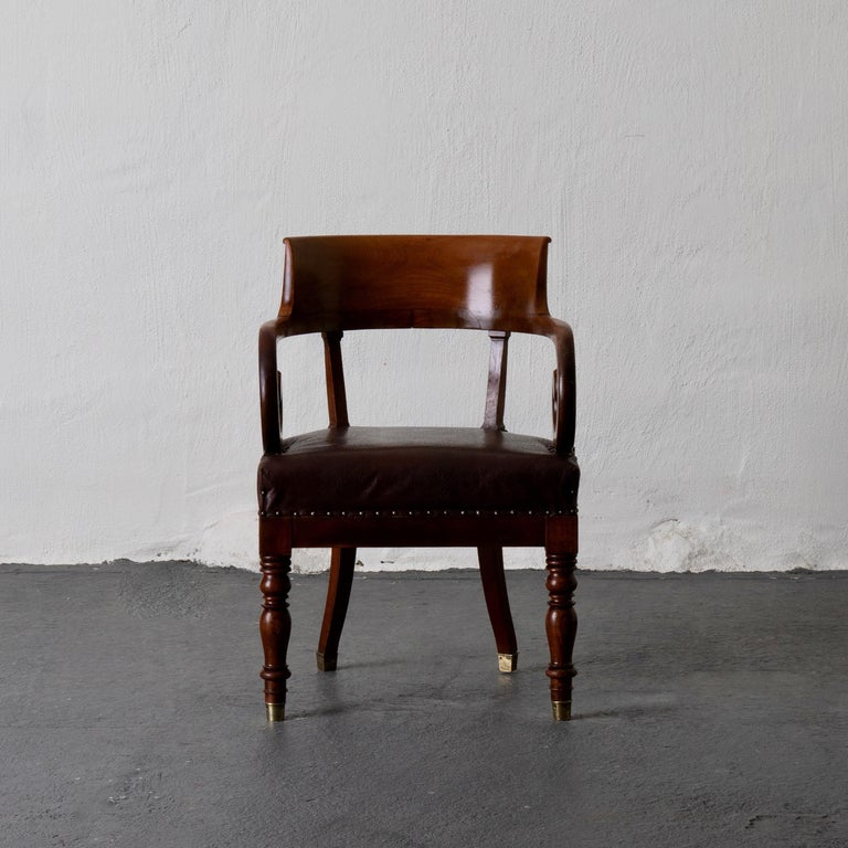 Chair desk Swedish mahogany brown Sweden. Armchair made during the early 19th century in Sweden. Frame made from dark brown mahogany. Curved back and spiral armrests.