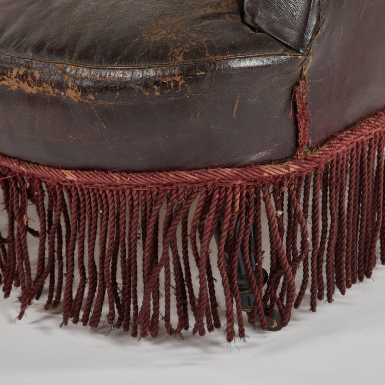 Early 20th century French leather armchair with fringe.