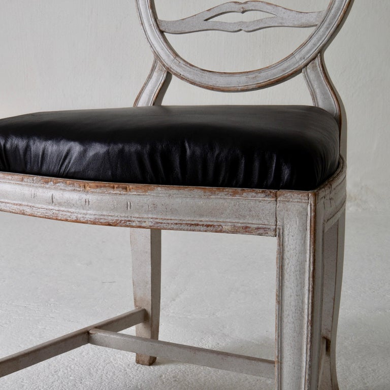 Chair Gustavian Swedish white black Sweden. A side chair made during the Gustavian period in Sweden 1790-1810. Beautiful carvings on the oval back. Square and tapered legs. Loose seat upholstered in a soft black leather.