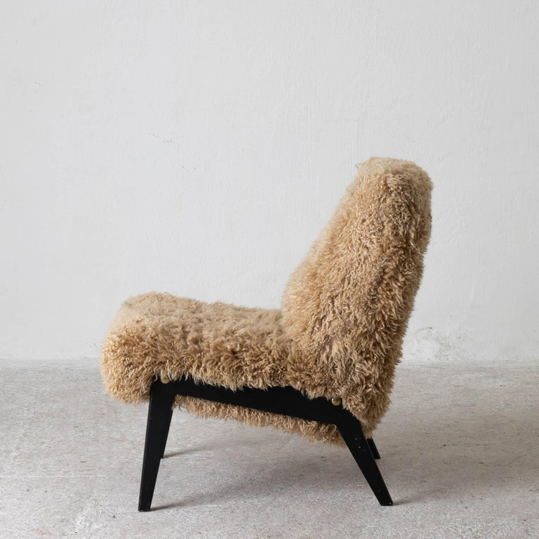 Chair Swedish Nordiska Kompaniet 20th century fur beige, Sweden. A lounge chair made during the 20th century by in Sweden. Reupholstered in a long haired golden colored fur. Black legs with brass screws.
