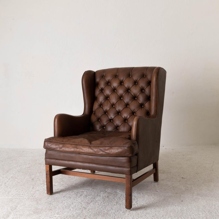 Chair wingback Swedish 20th century brown tufted, Sweden. A larger wingback chair made during the 20th century in Sweden. Upholstered in a brown leather with a tufted back. Square wooden legs.