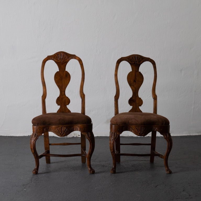A pair of beautiful Swedish Rococo side chairs from the west part of Sweden. Made during the Rococo period and upholstered in a chocolate brown suede.