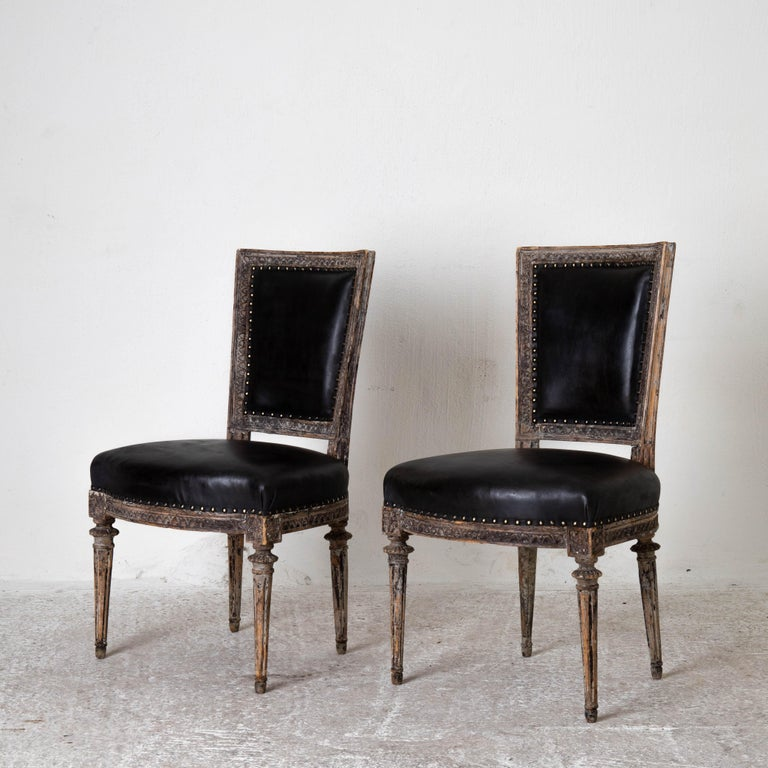Chairs side Sweden Gustavian period 1790-1810 black leather. A pair of side chairs made during the Gustavian period in Sweden 1790-1810. Frame stripped to its original paint with leaf tip carvings. Rounded and channeled legs. Seat and back