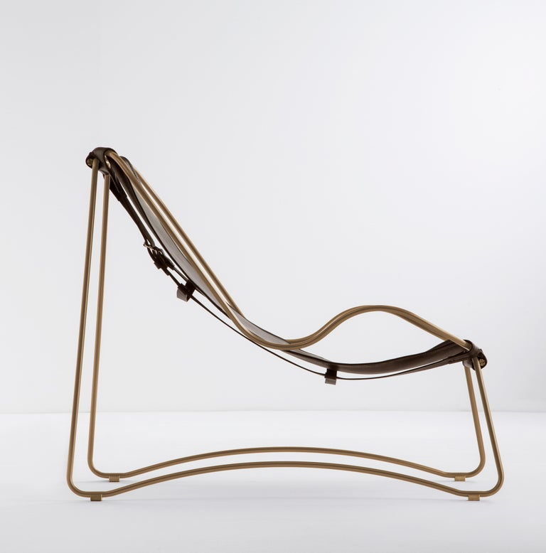 HUG Chaise Longue Aged Brass Steel and Vegetable Tanned Dark Brown  Leather  The Hug contemporary chaise lounge is designed and conceived with a light aesthetic, the slight oscillation of the steel rod of 16 mm is complemented by the flexibility of