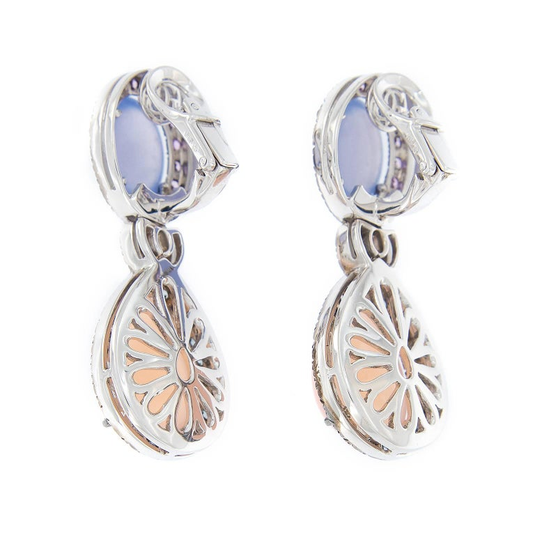 These lovely double drop earrings are a pretty display of pastels. Blue chalcedony and rose quartz are accented with pink and pastel blue sapphires. Earrings are constructed in 18k white gold with black rhodium. Weigh 31.1 grams.  Pink Sapphires