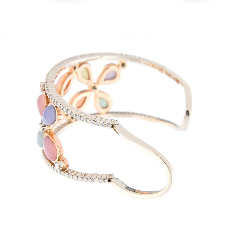 This 18k rose and white gold wide cuff bracelet features three open work floral designs with blue, pink and green chalcedony accented with over three carats of diamonds. Weighs 48.8 grams. Handmade in New York  Diamond 3.30 cttw