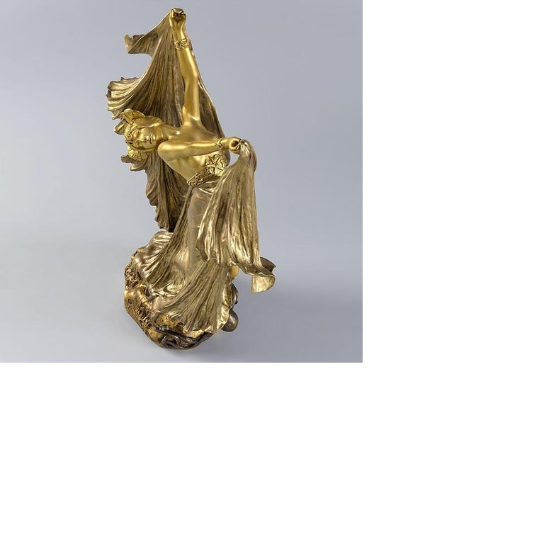 This gilt bronze figural sculpture by Louis Chalon depicts a dancing woman with an octopus at her feet, one of its tendrils wrapped intimately around her leg. Her rolling unfurled veils, imbuing her with exoticism, as her free-form dance movement