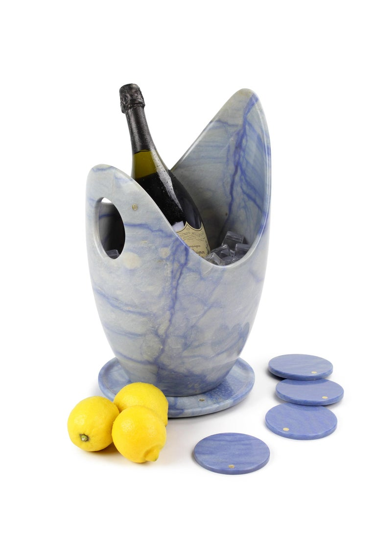 Luxurious and big Champagne bucket set sculpted by hand from a solid block of Azul Macaubas.  The set consisting of 1 Champagne bucket, 1 circular plate and 4 circular coasters. Polished finishing. Champagne bucket dimensions: D26 H 41 cm. Plate