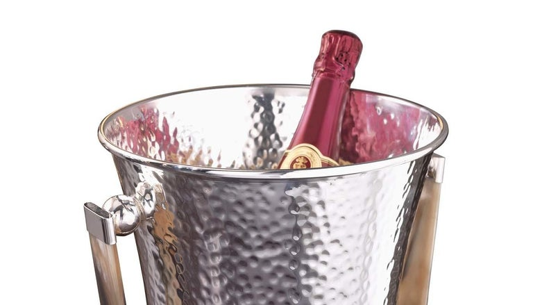 A timeless accessory for a cocktail cart or a bar cabinet in both classic and modern decors, this sophisticated champagne bucket will add glamour to formal dinners and entertaining events. Crafted of silver plated brass entirely hand-chiseled with