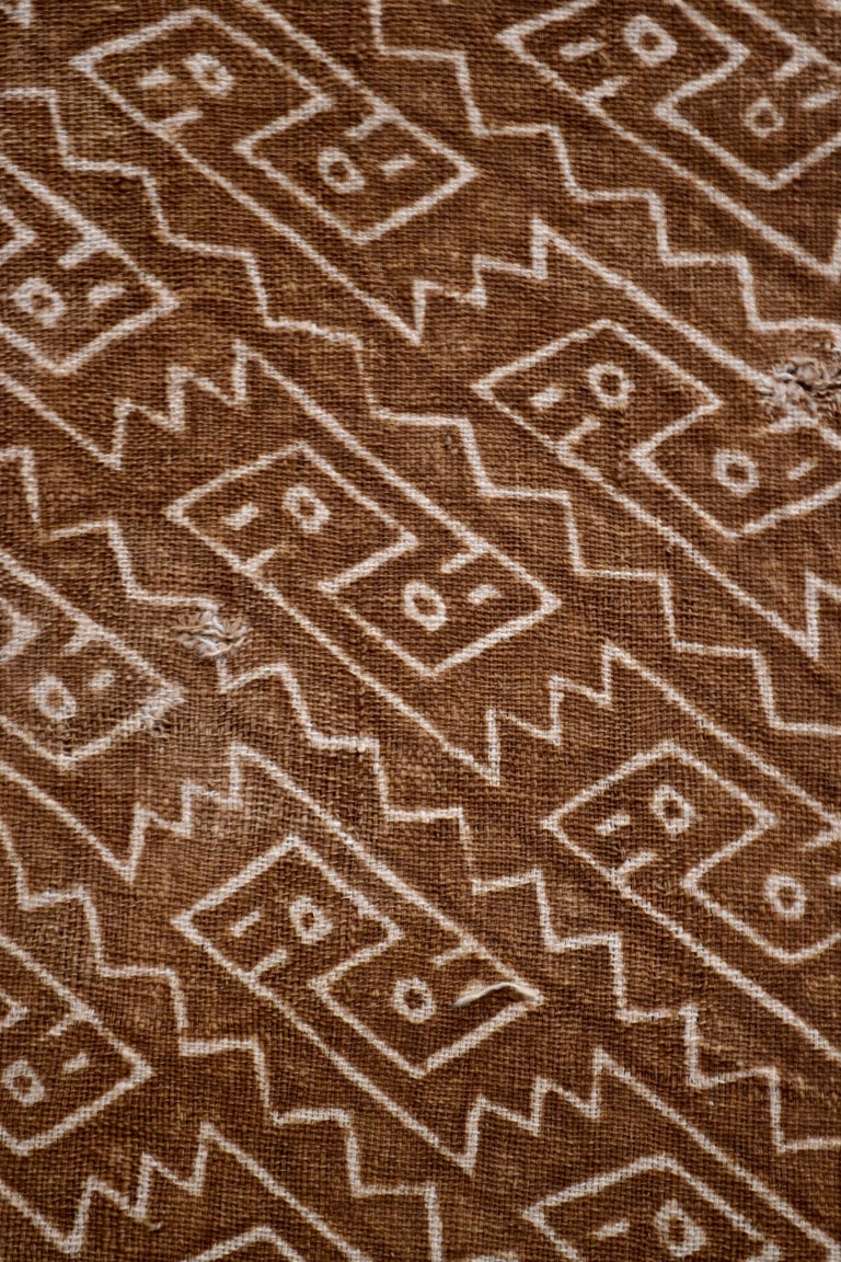 Earth tones textile fragment. Puzzle like figures painted above a light pink stripe.  It is a wonder to behold antiquities such as a pre-Columbian textiles, an authentic piece of art that has been preserved for centuries and that survives