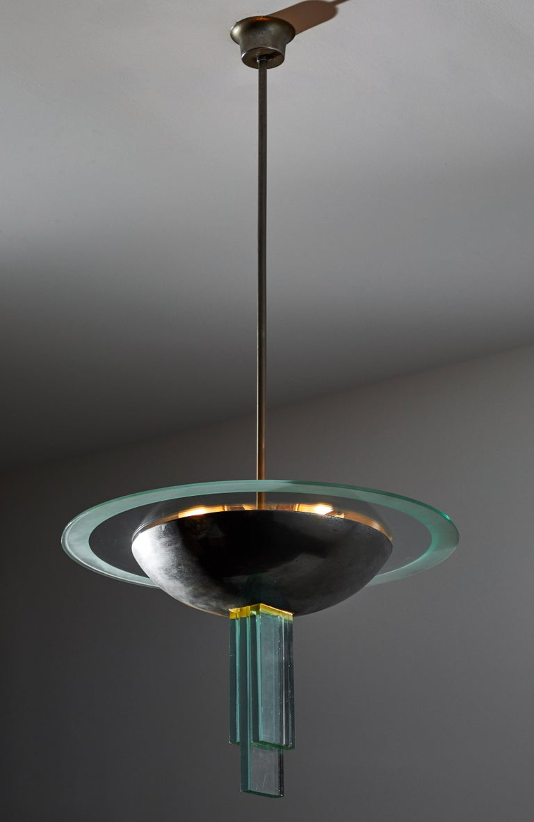 Chandelier attributed to Pietro Chiesa for Fontana Arte. Designed and manufactured in Italy, circa 1946. Naturally patinated, nickel plated steel and glass. Interior of nickel shade and three glass structures at base of light illuminate. Rewired for
