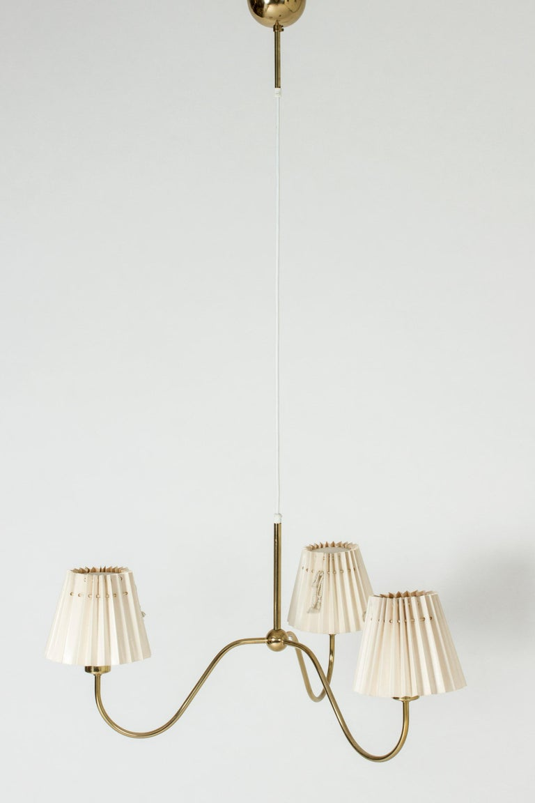 Three-armed chandelier by Josef Frank, made from brass. Wide, elegant design with a decorative ball at the center of the undulating arms. Original shades in good condition.
