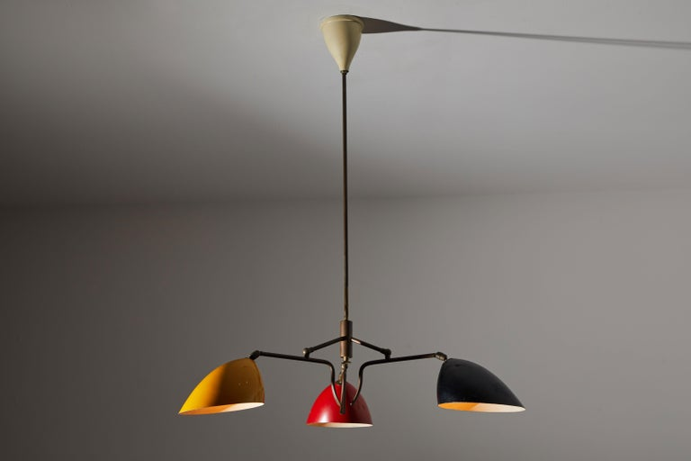 Three-arm chandelier by Lumen. Manufactured in Italy, circa 1950s. Brass and enameled metal. Shades articulate in various positions. Rewired for US junction boxes. Original canopy. Takes three E27 60w maximum bulbs.