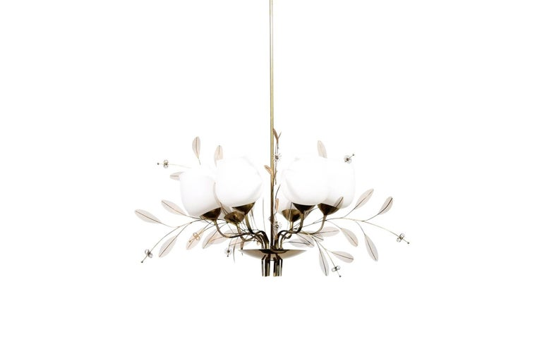 Chandelier model 9029/6 by Finnish designer Paavo Tynell for Taito Oy. This fixture features six glass diffusers and numerous brass floral features and mesh leaves. Central component impressed with model number,