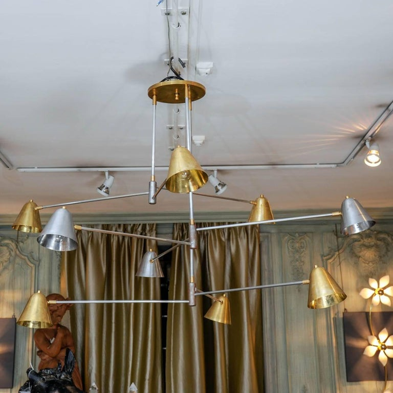 This chandelier is a creation of the Studio Glustin. It is made of brass and steel, and composed by nine lights with rotative metal lampshades.