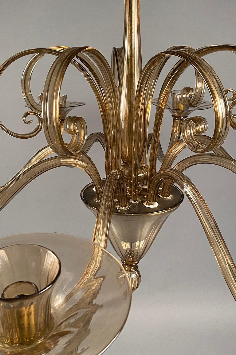 Amber colored 8-arm chandelier with 8 scrolled elements extending upwards from the center.  Non-UL electrified with candelabra sockets.
