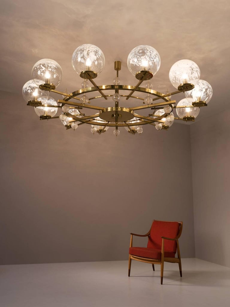 Chandelier, in brass and glass, European, 1970s.  Extreme large chandelier with brass fixture and art-glass. The chandelier with brass frame consist of twelve-light, formed in a circle, with glass shades. The pleasant light it spreads is very